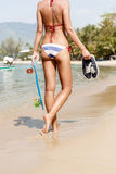 Sexy suntanned lady with the blue penny board walks along the be Stock Image
