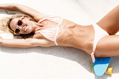 Sexy suntanned lady lying on the blue penny board in the park Stock Image