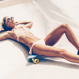 Sexy suntanned lady lying on the blue penny board in the skate p Stock Images