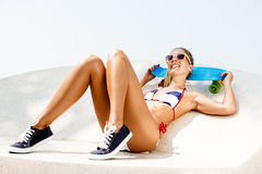 Sexy suntanned lady sitting with blue penny board on the beach Stock Image
