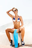Sexy suntanned lady sitting with blue penny board on the beach Royalty Free Stock Image