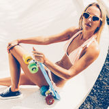 Sexy suntanned lady sitting with blue penny board on the beach Royalty Free Stock Photo