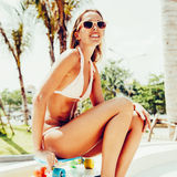 Sexy suntanned lady sitting on the blue penny board in the park Royalty Free Stock Images