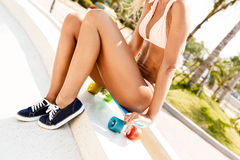 Sexy suntanned lady sitting on the blue penny board in the park Royalty Free Stock Photography