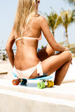 Sexy suntanned lady sitting on the blue penny board in the park Royalty Free Stock Photo