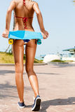 Sexy suntanned lady staying with blue penny board on the streat Royalty Free Stock Photos