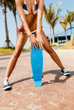 Sexy suntanned lady staying with blue penny board on the streat Stock Image