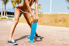 Sexy suntanned lady staying with blue penny board on the streat Royalty Free Stock Images