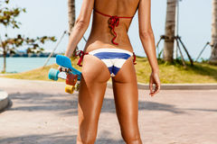 Sexy suntanned lady staying with blue penny board on the streat Stock Images