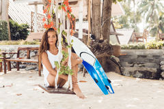 surfer girl on swing at tropical beach. Royalty Free Stock Photo