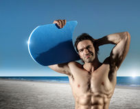 Surfer guy. Fun portrait of a young muscular male surfer on the beach with blue sky and ocean in background stock photo