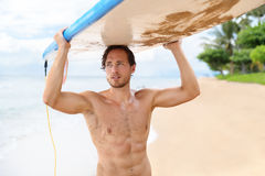 Sexy surfer man holding surf board after surfing. Sexy active watersport fitness abs man carrying his surfboard on the head. Surfer lifestyle on Hawaii beach Stock Photos
