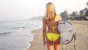 A sexy surfer woman in a swimsuit is walking along the beach with a surfboard