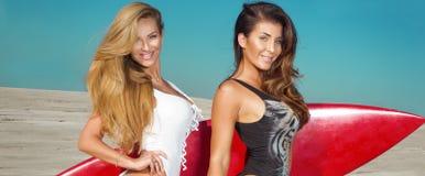 Sexy surfers, meisjes op het strand Royalty-vrije Stock Afbeeldingen