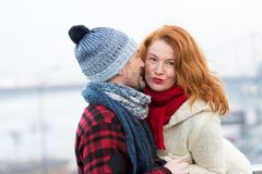 woman listen to men. Happy woman from male story. Man whispers to red hair woman. Close up of couple at date. stock photography