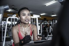 Sexy and sweaty Asian woman training hard at gym using elliptical pedaling machine gear in intense workout. Young sexy and sweaty Asian woman training hard at Royalty Free Stock Photography