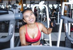 and sweaty Asian woman training hard at gym using elliptical pedaling machine gear in intense workout Royalty Free Stock Photos