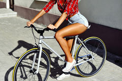 Sexy tan sporty young woman on a bicycle Royalty Free Stock Images