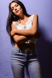 Sexy tanned brunette girl in a white vest and jeans Stock Photography