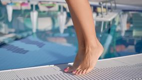 Sexy tanned female feet walking near swimming pool enjoying summer travel vacation close-up