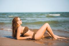 Sexy tanned girl in a bathing suit lies on the seashore. Beautiful tanned body in a beige swimsuit Royalty Free Stock Photos