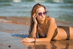 Sexy tanned girl in a bathing suit lies on the seashore. Beautiful tanned body in a beige swimsuit Royalty Free Stock Photography