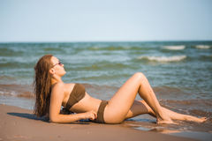 Sexy tanned girl in a bathing suit lies on the seashore. Beautiful tanned body in a beige swimsuit Royalty Free Stock Image