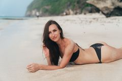 Tanned girl in black swimsuit posing on sandy beach near ocean. Beautiful model sunbathes and rests.  stock image