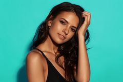 Sexy tanned girl in black swimsuit. Young sexy slim tanned woman in black swimsuit posing against blue background. Closeup Fashion portrait of beautiful girl Stock Image