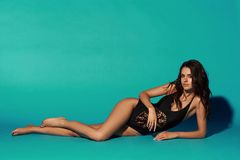 Sexy tanned girl in black swimsuit. Young sexy slim tanned woman in black swimsuit posing and lying on blue background. Fashion portrait of beautiful girl with Stock Photography