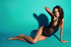 Sexy tanned girl in black swimsuit. Young sexy slim tanned woman in black swimsuit posing and sitting on blue background. Fashion portrait of beautiful girl with Royalty Free Stock Images