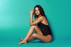 Sexy tanned girl in black swimsuit. Young sexy slim tanned woman in black swimsuit posing and sitting on blue background. Fashion portrait of beautiful girl with Stock Image