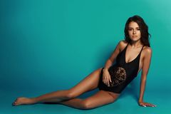 Sexy tanned girl in black swimsuit. Young sexy slim tanned woman in black swimsuit posing and sitting on blue background. Fashion portrait of beautiful girl with Stock Images