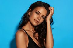 Sexy tanned girl in black swimsuit. Young sexy slim tanned woman in black swimsuit posing against blue background. Closeup Fashion portrait of beautiful girl Royalty Free Stock Image