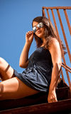 Sexy tanned girl in sunglasses sitting on metal stairs outdoor Stock Image