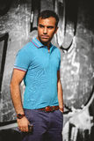Sexy tanned man in blue shirt posing against concrete wall Stock Images