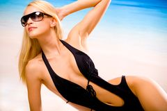 Sexy tanned woman on beach. Young beautiful sexy tanned happy woman in sunglasses and bikini laying during sunbath on sea beach Stock Photos