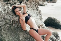 Tanned woman in black swimsuit posing on rocky beach. Girl with perfect body relaxing on tropical island at summer day. Concept vacation, travel, swimwear royalty free stock photography