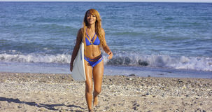 Sexy tanned woman walking with her surfboard Royalty Free Stock Photos