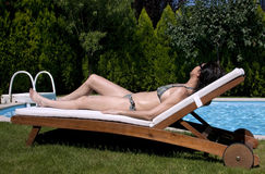Sexy Tanning woman near the pool  Royalty Free Stock Photography