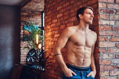 A handsome man with BMX in a studio. A tattoed shirtless man leans against the brick wall. Smiling and looking away royalty free stock photo