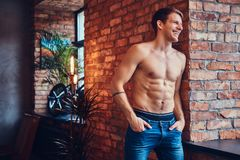 A handsome man with BMX in a studio. A tattoed shirtless man leans against the brick wall. Smiling and looking away royalty free stock image