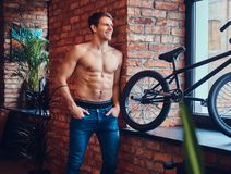 A handsome man with BMX in a studio. A tattoed shirtless man leans against the brick wall. Smiling and looking away royalty free stock photography