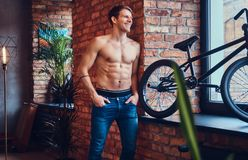 A handsome man with BMX in a studio. A tattoed shirtless man leans against the brick wall. Smiling and looking away stock photos