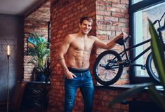 A handsome man with BMX in a studio. A tattoed shirtless man leans against the brick wall. Smiling and looking away royalty free stock photos