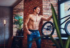 A handsome man with BMX in a studio. A tattoed shirtless man leans against the brick wall. Smiling and looking away stock photography