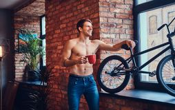 A handsome man with BMX in a studio. A tattoed shirtless man leans against the brick wall. Smiling and looking away stock images