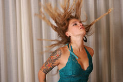 Tattoo girl. Pretty girl with tattoo on her arm flipping her hair stock photos
