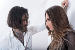 Sexy tattooed man approaching a young woman. Sexy tattooed men approaching a young women on white background Stock Images