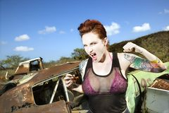 Sexy tattooed woman. Angry tattooed Caucasian woman yelling with fists clenched in junkyard Royalty Free Stock Images